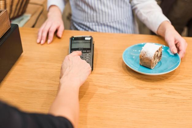 おいしいケーキのスライスの請求書を支払うためにピン機を使用して顧客のクローズアップ