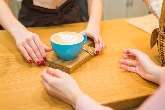 木製のテーブルで顧客にカフェラテアート泡とコーヒーカップを与えるウェイトレスのクローズアップ
