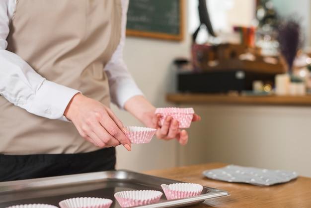 木製のテーブルのベーキングトレイにカップケーキケースを配置する女性のパン屋さんの手のクローズアップ