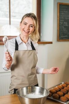 コーヒーショップで泡立て器でクリームを保持している若い女性を笑顔