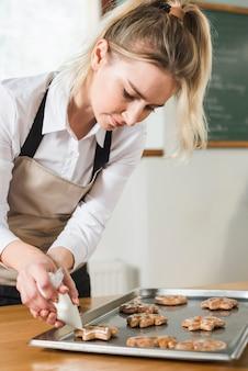 ベーキングトレイ上の焼きたてのクッキーにクリームを適用する