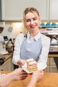 コーヒーショップで女性客にペストリーケーキを提供する若い女性の笑みを浮かべてください。