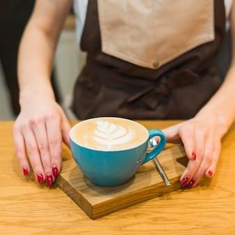 カフェテリアで木製のまな板でコーヒーを提供している女性バリスタのクローズアップ