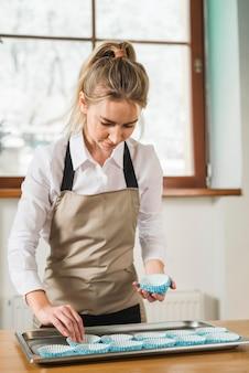 Молодая женщина, поместив пустые выпечки чашки в лоток на деревянный стол