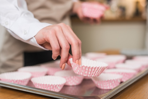 トレイにカップケーキケースを置く女性のパン屋の手