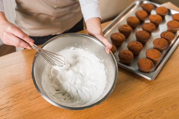女性のオーバーヘッドビューは、木製のテーブルの上にボウルにクリームを作るための泡立て器で卵白をホイップクリーム