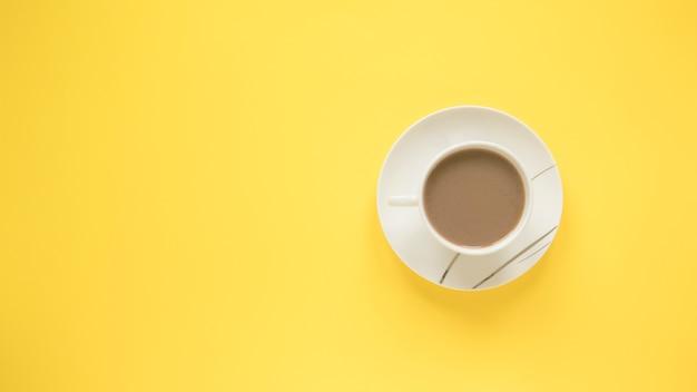 明るい黄色の背景の上の受け皿とホットコーヒーのカップ