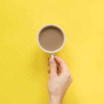黄色の背景に一杯のコーヒーを持っている人の手のクローズアップ