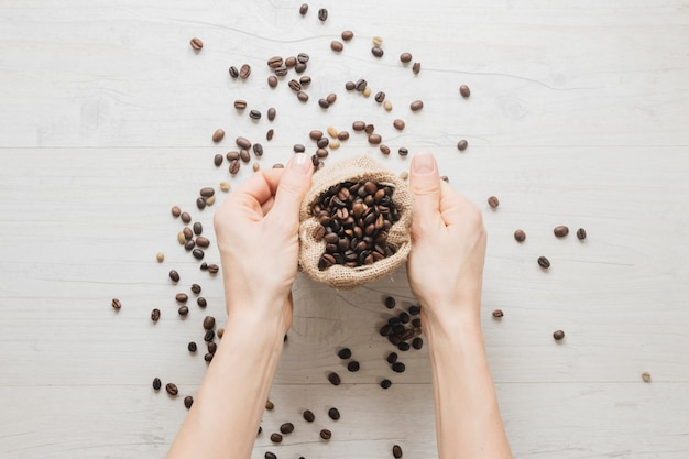 Рука небольшой мешок с кофе в зернах на деревянный стол
