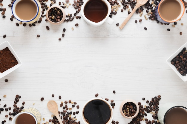Различные виды кофе; сырые кофейные зерна; жареные кофейные зерна; кофейный порошок на белом столе