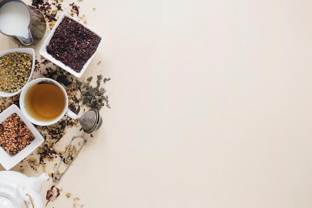Лимонный чай с сухими чайными листьями; высушенные цветы китайской хризантемы; чайное ситечко; молоко; травы и чайник на цветном фоне