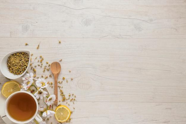 乾燥中国の菊の花と織り目加工の木製テーブルの上のレモンティーとレモンのスライス