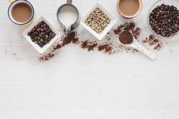 木製のテーブルの上のコーヒーカップと生と焙煎のコーヒー豆のトップビュー
