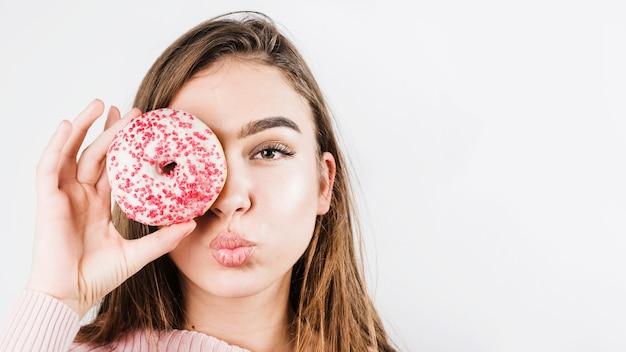 唇をふくれっ面と白い背景で隔離のドーナツで目を覆っている若い女性のクローズアップの肖像画
