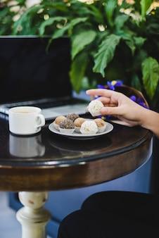 コーヒーとラップトップのラウンド木製テーブルの上の人の手のチョコレートボールのクローズアップ