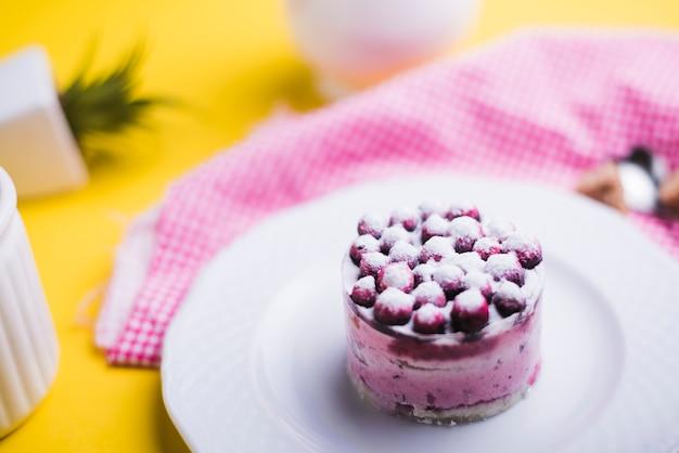 黄色の背景に白い皿に新鮮なブルーベリー