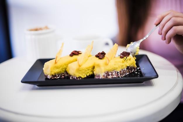 白いテーブルの上の黒いトレイにスプーンでケーキのスライスを食べる女性の手のクローズアップ
