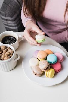 テーブルの上のカップにコーヒーと茶色の砂糖の立方体とマカロンを持っている女性の手のクローズアップ