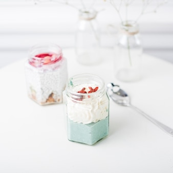 白いテーブルの上のガラスの瓶に新鮮なフルーツスムージー