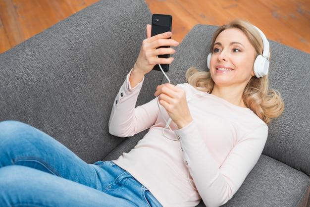 Улыбается молодая женщина, глядя на мобильный телефон прослушивания музыки на наушники