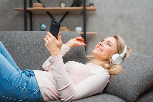 手で携帯電話を保持しているヘッドフォンで音楽を楽しんでのんきな若い女性