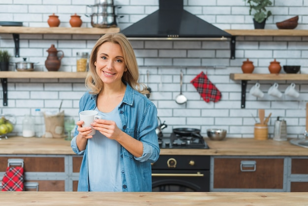 若い女性が台所で手に立っているコーヒーマグ