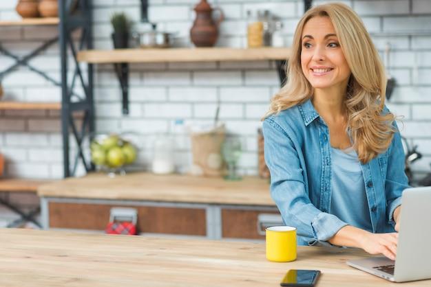 Белокурая молодая женщина печатая на компьтер-книжке с кофейной чашкой и сотовым телефоном на таблице