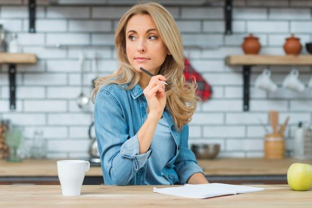 木製のテーブルの上のノートに書いている間思考金髪の若い女性