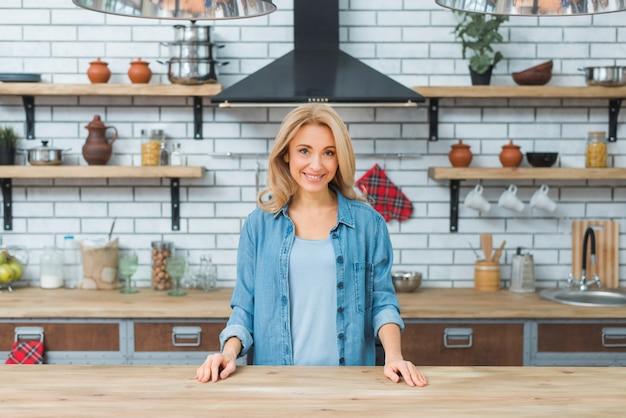 台所の木製のテーブルの後ろに立っている笑顔の若い女性