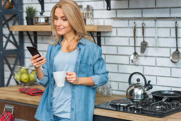 Улыбаясь блондинка молодая женщина, держащая чашку кофе, глядя на мобильный телефон