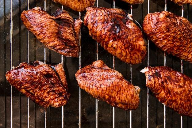 Вид сверху на вкусные кусочки куриного мяса на металлическом гриле