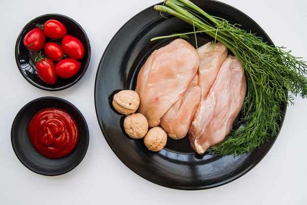 生の鶏肉の立面図。新鮮なディル。クルミトマトと白い背景の上のソース