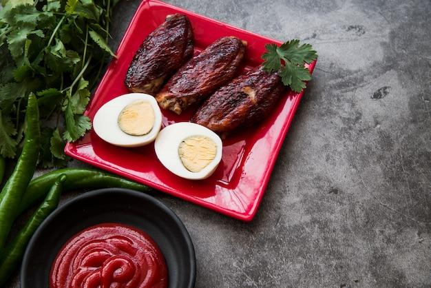 Вареное яйцо и томатный соус и ингредиенты на грубом фоне