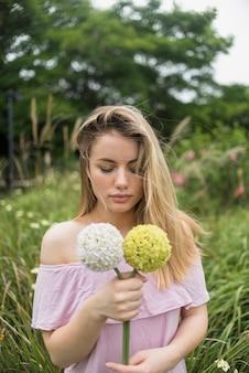 手に花を持ったドレスの若い女性