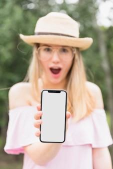 空白の画面を持つスマートフォンを持って驚く女性