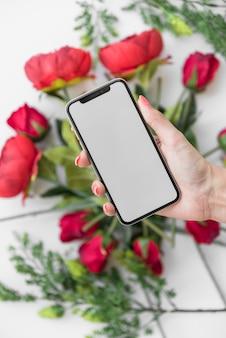 バラの上の空白の画面を持つスマートフォンを持つ女性