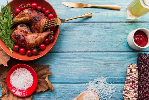 Вкусная жареная курица на ужин с пивом; поваренная соль; соус; кукуруза и помидоры черри на столе