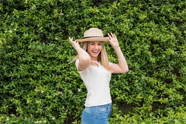 緑の芝生の近くの帽子で笑顔の女性