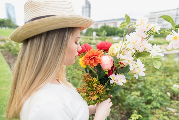 Дама в шляпе с букетом цветов в городском парке