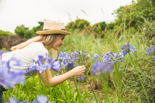 公園の青い花の近くの帽子で陽気な女性