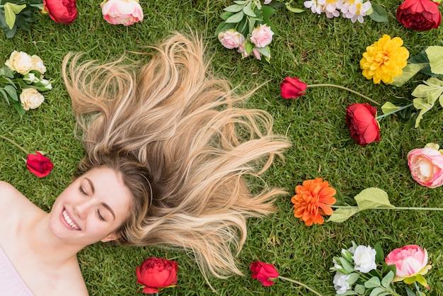 Веселая дама лежит на траве между цветами