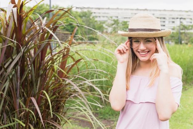 眼鏡と帽子の高い草の近くで笑顔の女性