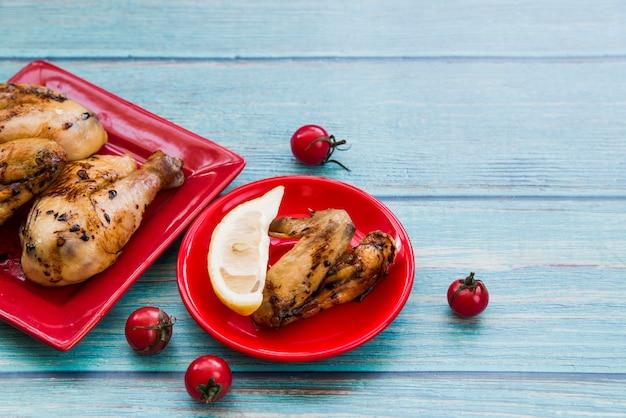 Жареные куриные ножки и куриные крылышки в красной тарелке с помидорами и ломтиком лимона на синем столе