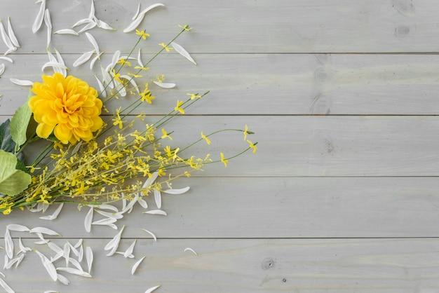 灰色の木製の机の上の黄色い花