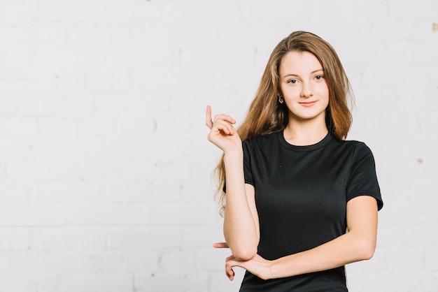 Портрет улыбающегося девочки-подростка, стоящей на белой стене