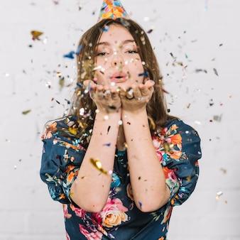 Девочка-подросток дует конфетти из рук на белом фоне