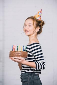 Портрет улыбающейся девочки-подростка, держащей шоколадный торт с разноцветными свечами