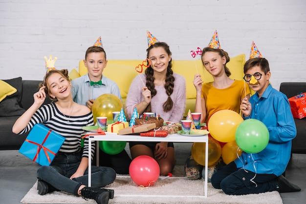 誕生日パーティーを楽しんでいる小道具を持っている友人のグループ