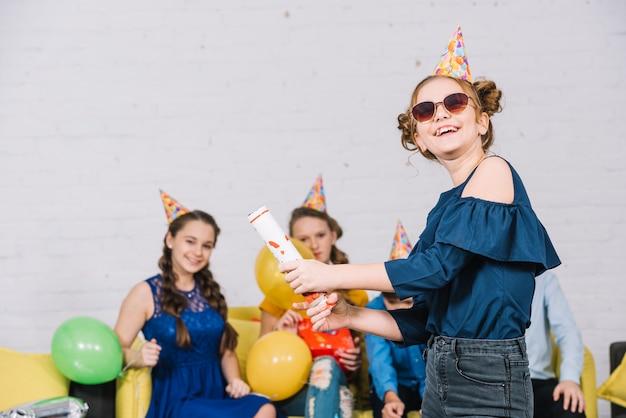 Девочка-подросток, отпуская вечеринку поппер, стоя перед ее друзьями, наслаждаясь вечеринку