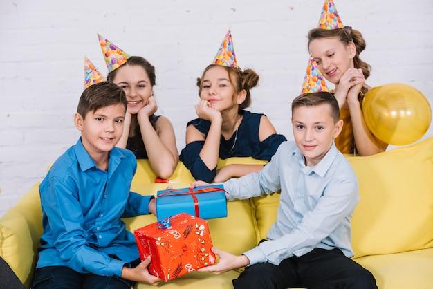 Девочки, стоящие за диваном и смотрящие на двух подростков, держащих подарочные коробки